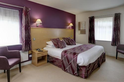 A bed or beds in a room at Best Western Plus Sheffield Mosborough Hall Hotel