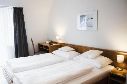 A bed or beds in a room at Hotel Blaue Traube