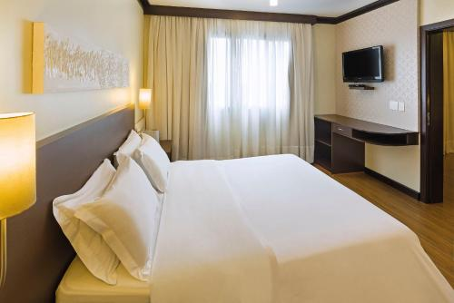 A bed or beds in a room at Swan Tower Caxias do Sul