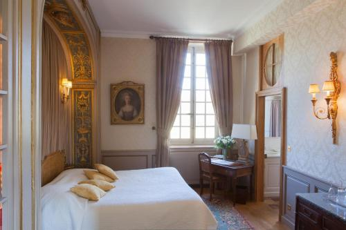 A bed or beds in a room at Château-Hôtel de Bourron