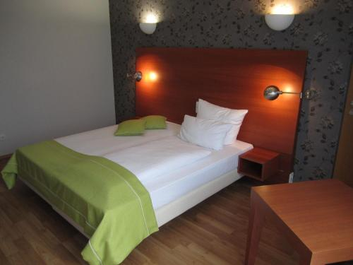 A bed or beds in a room at PRIMA Hotel Schloss Rockenhausen