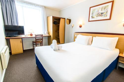 A bed or beds in a room at Campanile Manchester