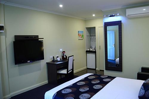 A television and/or entertainment center at Park Squire Motor Inn & Serviced Apartments