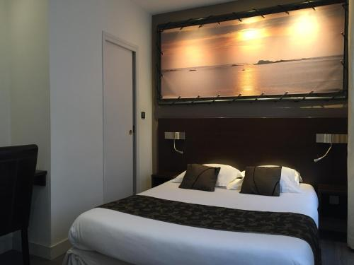 A bed or beds in a room at Hotel Le Croiseur Intra Muros