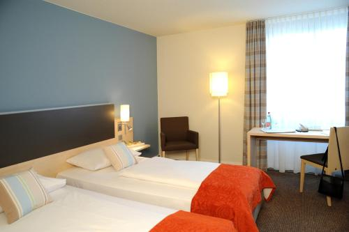 A bed or beds in a room at Mercure Bonn Hardtberg