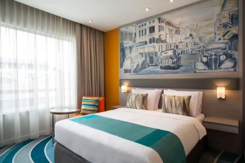 A bed or beds in a room at Mercure Jakarta Cikini