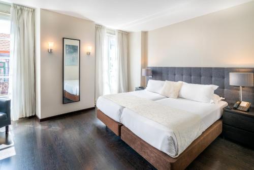 Rossio Garden Hotel tesisinde bir odada yatak veya yataklar