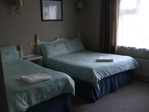 A bed or beds in a room at Harmony Inn - Glena House