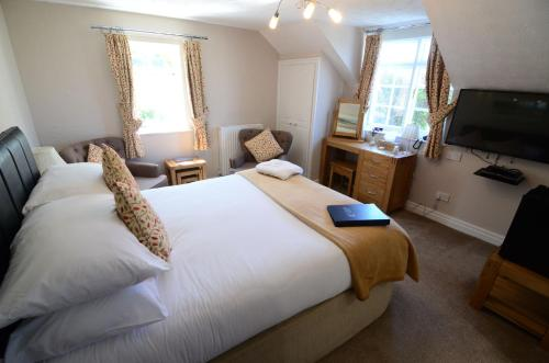 A bed or beds in a room at Ellerby Country Inn