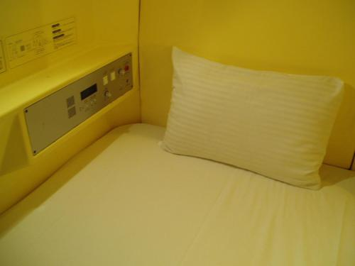 A bed or beds in a room at Capsule Hotel & Sauna Ikebukuro Plaza