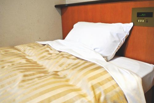 A bed or beds in a room at Kakegawa Business Hotel Ekinan-inn