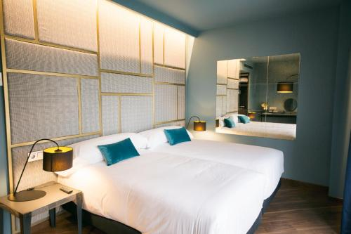 A bed or beds in a room at Pamplona Catedral Hotel
