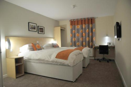 A bed or beds in a room at Royal George Hotel