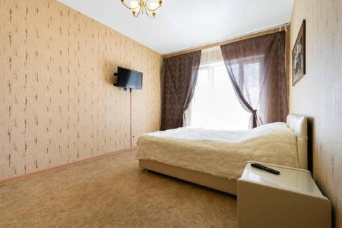 Кровать или кровати в номере Apartment Izhorskogo Batalyona 11