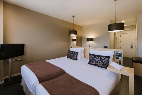 A bed or beds in a room at Rafaelhoteles Forum Alcala