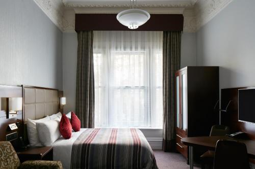 A bed or beds in a room at The Grand at Trafalgar Square