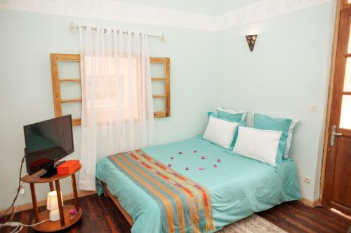 A bed or beds in a room at Maison Lovasoa