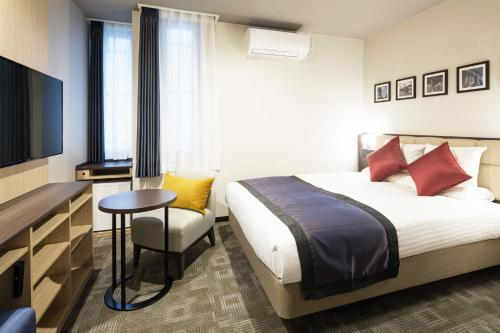 A bed or beds in a room at HOTEL MYSTAYS Kanda