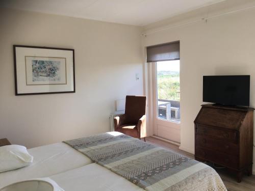 Een bed of bedden in een kamer bij Hèt Duinappartement