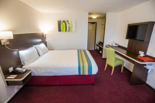 A bed or beds in a room at Ramada London South Mimms
