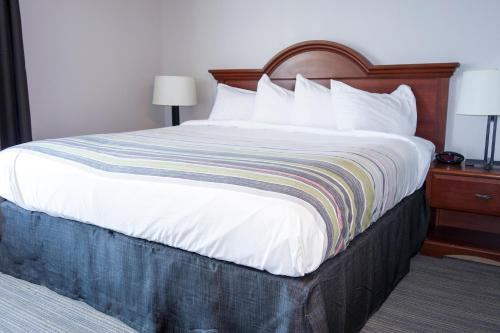 A bed or beds in a room at Country Inn & Suites by Radisson, Dahlgren, VA