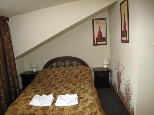 A bed or beds in a room at Hotelik Korona