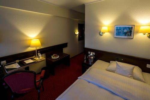 A bed or beds in a room at Sachsenwald Hotel Reinbek