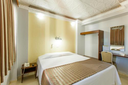 A bed or beds in a room at Mirante Hotel