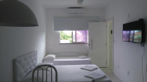A bed or beds in a room at Cabo Frio Flats