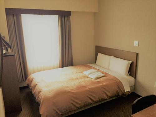 A bed or beds in a room at Hotel Crown Hills Yamagata