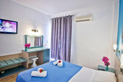 A bed or beds in a room at Argo Hotel