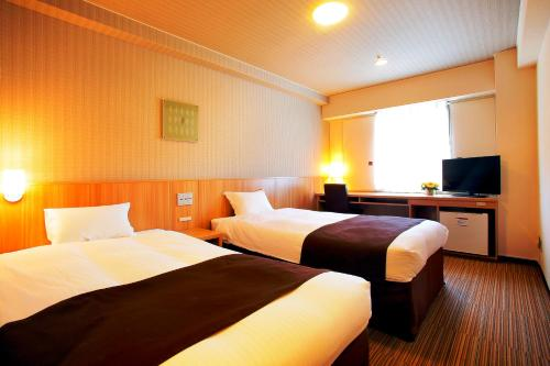 Tempat tidur dalam kamar di Nest Hotel Sapporo Ekimae