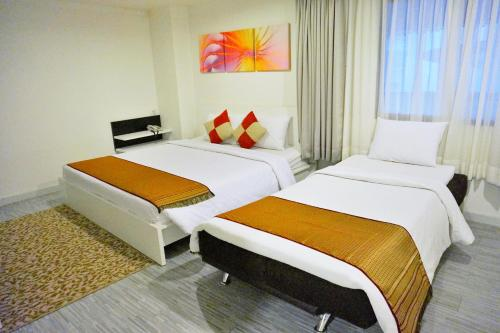 A bed or beds in a room at Pratunam City Inn