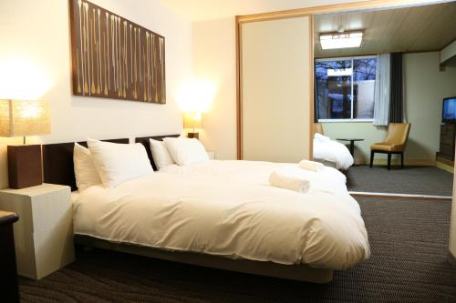 A bed or beds in a room at Hakuba Echo Hotel