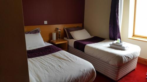 A bed or beds in a room at Dunbur Lodge
