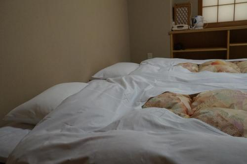 A bed or beds in a room at Annex Katsutaro Ryokan