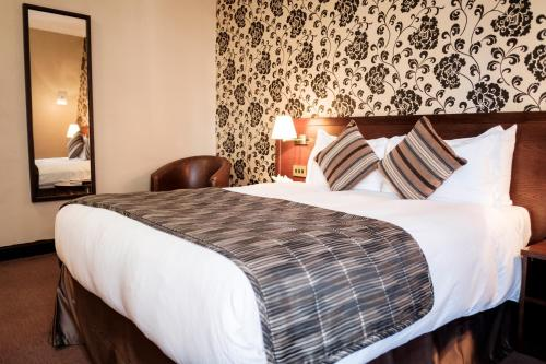 A bed or beds in a room at The Sanctuary House Hotel