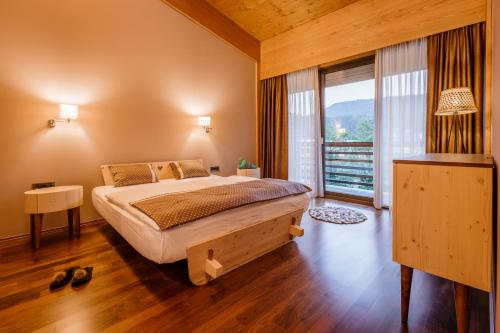 A bed or beds in a room at Bohinj Eco Hotel