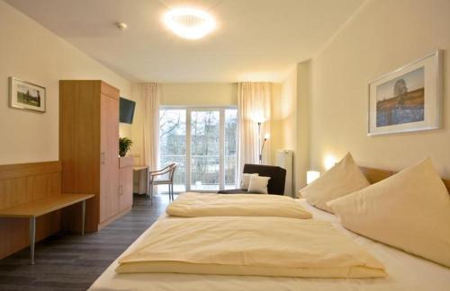 A bed or beds in a room at Haller Hotel Garni