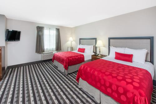 A bed or beds in a room at Ramada by Wyndham Springfield North