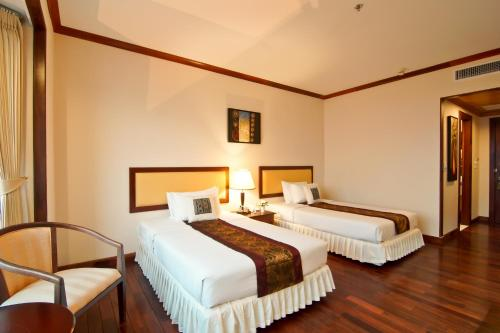 A bed or beds in a room at Champasak Grand Hotel