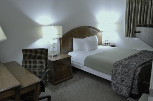 A bed or beds in a room at Rodeway Inn & Suites Ocean Beach
