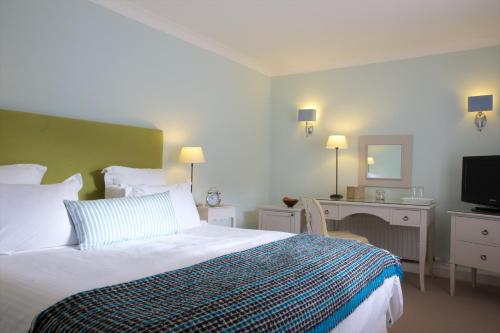 A bed or beds in a room at Lugger Hotel 'A Bespoke Hotel'