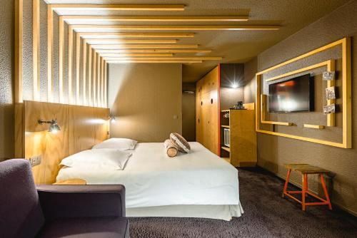 A bed or beds in a room at Hôtel Le Refuge des Aiglons