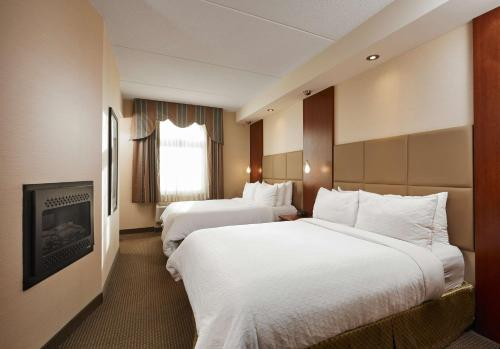 A bed or beds in a room at Best Western Plus Orangeville Inn & Suites