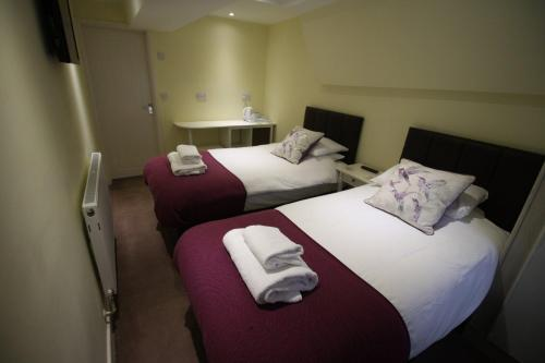 A bed or beds in a room at The Old Bear Inn