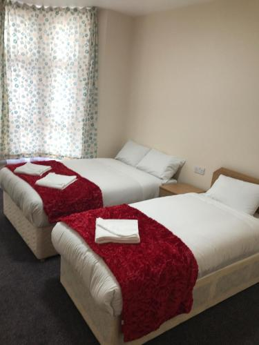 A bed or beds in a room at Woodlands Lodge Ilford
