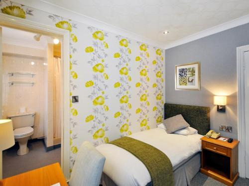 A bed or beds in a room at Ardington Hotel