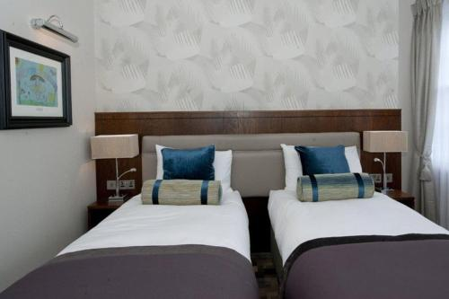 A bed or beds in a room at The Greenwood Hotel - Wetherspoon
