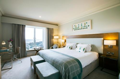 A bed or beds in a room at Portmarnock Hotel & Golf Links